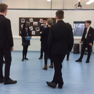 Image of a 'Presentation, confidence and resilience' workshop with Year 11 students; students are stood in a circle with one holding a ball